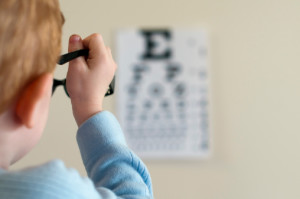 Young Boy Reading From Eye Chart